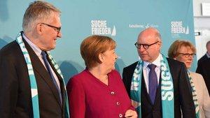 Die Schals, die Thomas Sternberg (links) und Markus Lewe auf diesem Foto mit Kanzlerin Angela Merkel tragen, sind nun im Stadtmuseum. | Foto: Michael Bönte