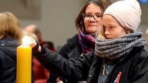 Gläubige entzünden Kerzen in Münsters Überwasserkirche und beten still für den Frieden