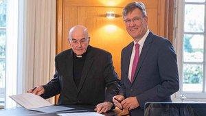 Bischof Felix Genn und Uni-Rektor Johannes Wessels unterzeichnen den Vertrag zur Studie. | Foto: Christof Haverkamp