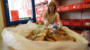 Eine Mitarbeiterin sortiert Brot und Brötchen. | Foto: Michael Bönte
