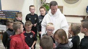 Kinder im Trainingsanzug gratulieren Pater Philip Muryne nach der Priesterweihe.