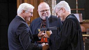 Bundespräsident Frank-Walter Steinmeier erhält ein Kreuz von Kardinal Reinhard Marx und Bischof Heinrich Bedford-Strohm (von links). | Foto: epd