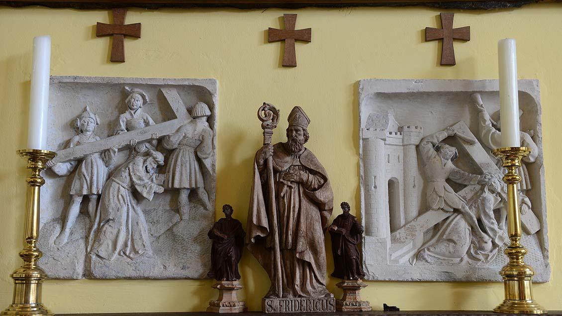 Heiligenfigur und Kreuzweg.