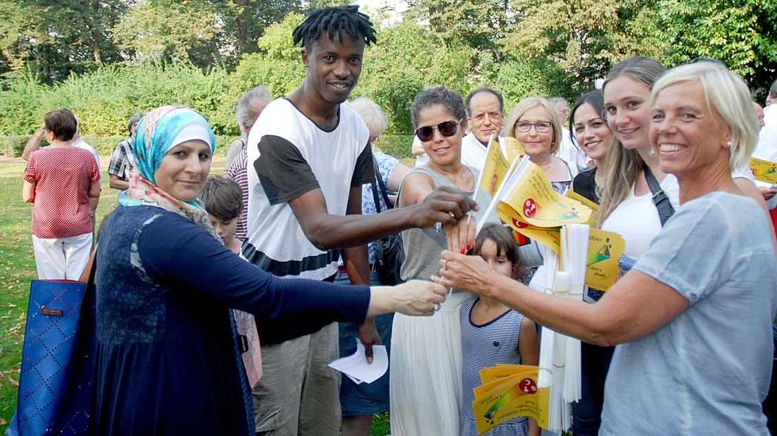 Im Kevelaerer Marienpark verteilten die Initiatoren Fähnchen als identitätsstiftendes Zeichen an die Teilnehmer der zweiten Interreligiösen Friedenswallfahrt.
