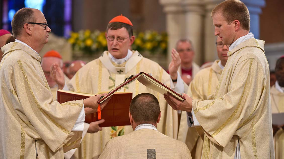 Kardinal Rainer Maria Woelki weiht Georg Bätzing (kniend) zum Bischof.