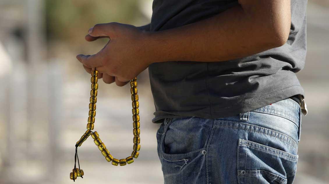 """Ein muslimischer Mann hält eine """"Misbaha"""" genannte Gebetskette in den Händen.Ein muslimischer Mann hält eine """"Misbaha"""" genannte Gebetskette in den Händen."""