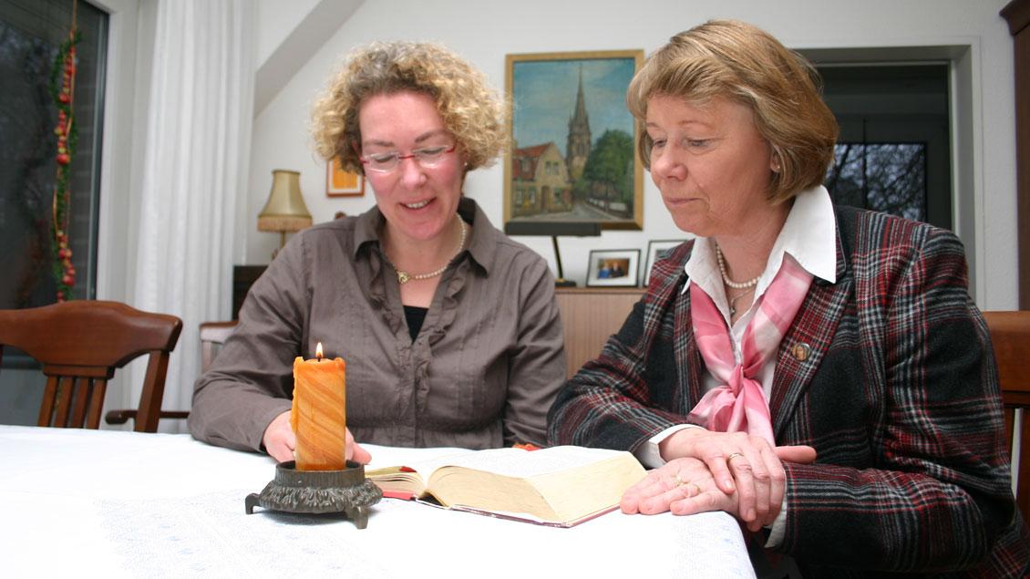 Zwei Frauen lesen die Bibel.