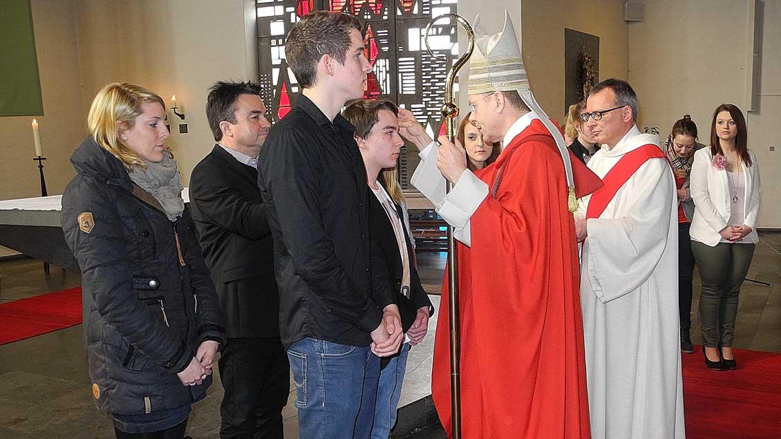 Weihbischof Stefan Zekorn firmt Jugendliche im Berufskolleg St. Michael.