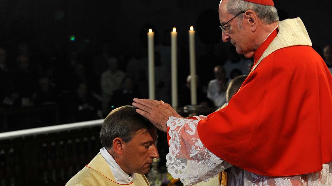 Segen für seine Aufgaben als Weihbischof: Kardinal Meisner legt Theising die Hände auf.