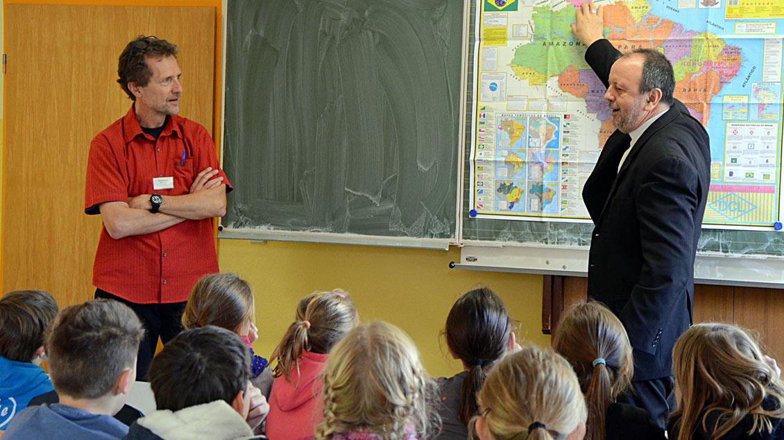 Norbert Bolte vom Hilfswerk Adveniat (links) vermittelt sprachlich zwischen dem Erzbischof Dom Roque Paloschi und den Grundschüler.