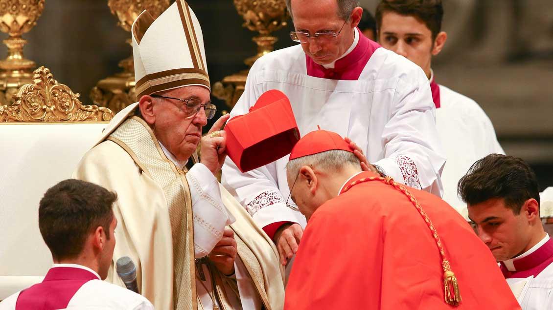 Papst Franziskus setzt dem neuen Kardinal Mario Zenari das Birett auf.