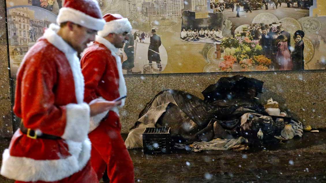 """Szene aus der """"Vorweihnachtszeit"""": Zwei Männer in Weihnachtsmann-Kostümen gehen an einem armen Mann im Schnee vorbei."""