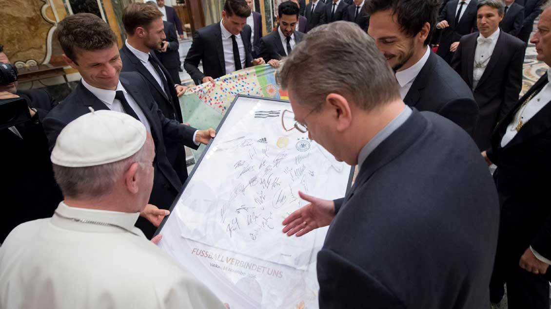 Die Spieler Thomas Müller (links) und Mats Hummels (rechts) überreichen Papst Franziskus ein signiertes Trikot der deutschen Fußballnationalmannschaft.