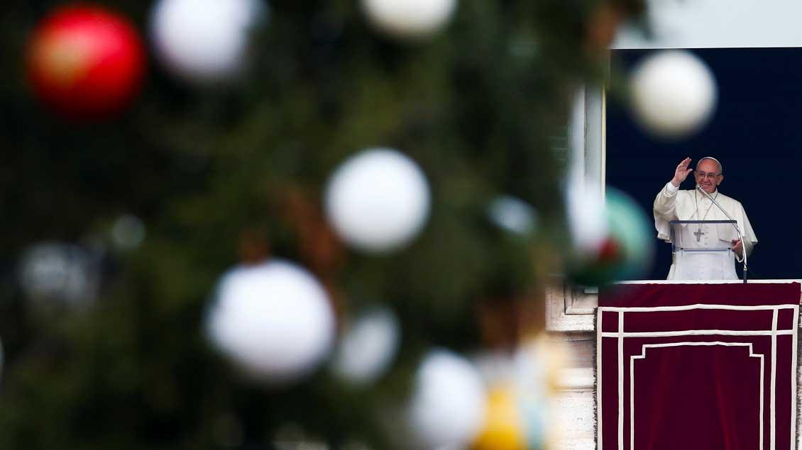 Auf dem Petersplatz steht schon der Weihnachtsbaum. Im Hintergrund begrüßt Papst Franziskus die Pilger.