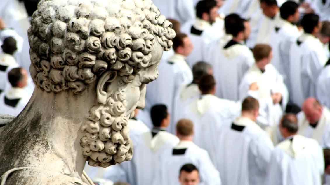 Priester unter dem Blick des heiligen Petrus auf dem Petersplatz in Rom. Foto: Markus Nolte