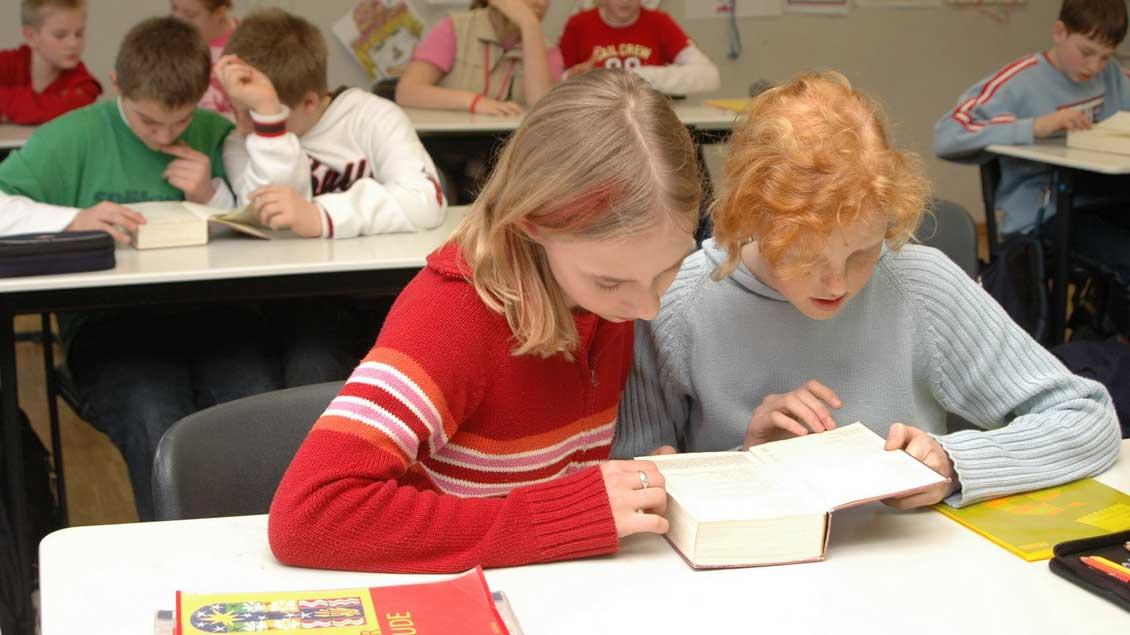 Schüler lesen im Religionsunterricht in der Bibel.
