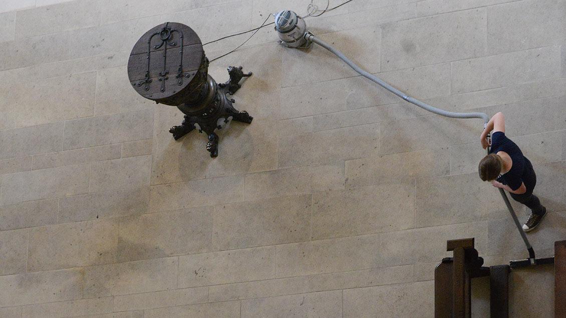 Arbeiten im Dom: Reinigungskraft neben dem Taufbecken im Westchor.