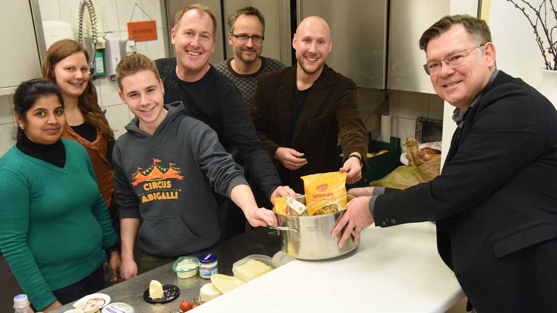 Markus Nolte (rechts), Stellvertretender Chefredakteur von Kirche+Leben, überreicht symbolisch einen Topf mit Nudeln an Thomas Mühlbauer (2. von rechts) und sein Team im Haus der Wohnungslosen in Münster.