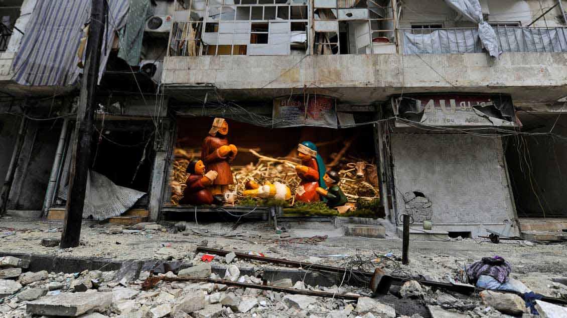 Eine Krippe, montiert in ein Foto aus der kriegszerstörten Stadt Aleppo.