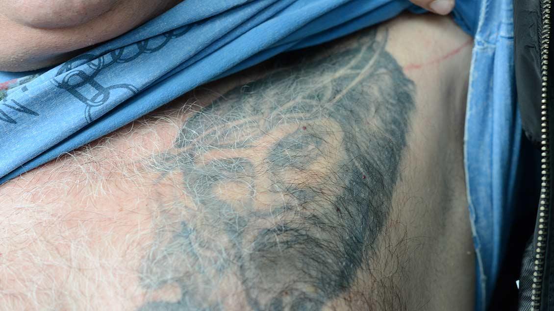 Jesus mit Dornenkrone. Tätowierung auf der Brust eines Mannes.