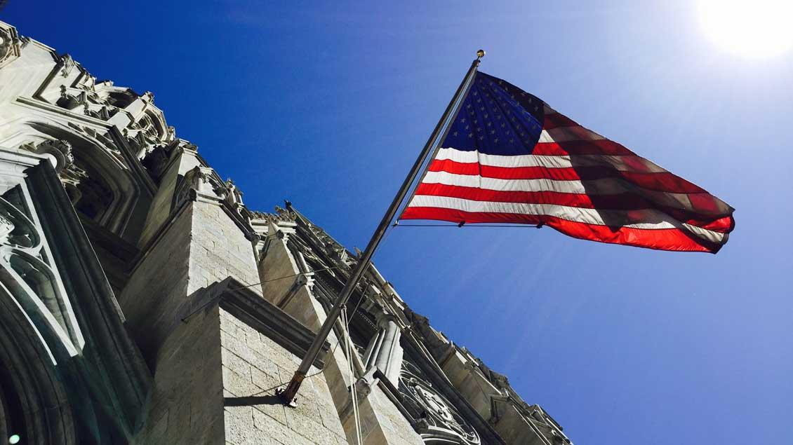 Die amerikanische Nationalflagge an der Fassade der katholischen Kathedrale St. Patrick in New York City.