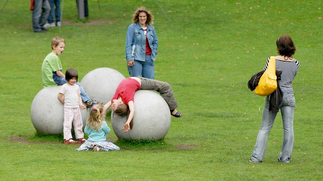Mütter schauen ihren Kindern beim Spielen zu.