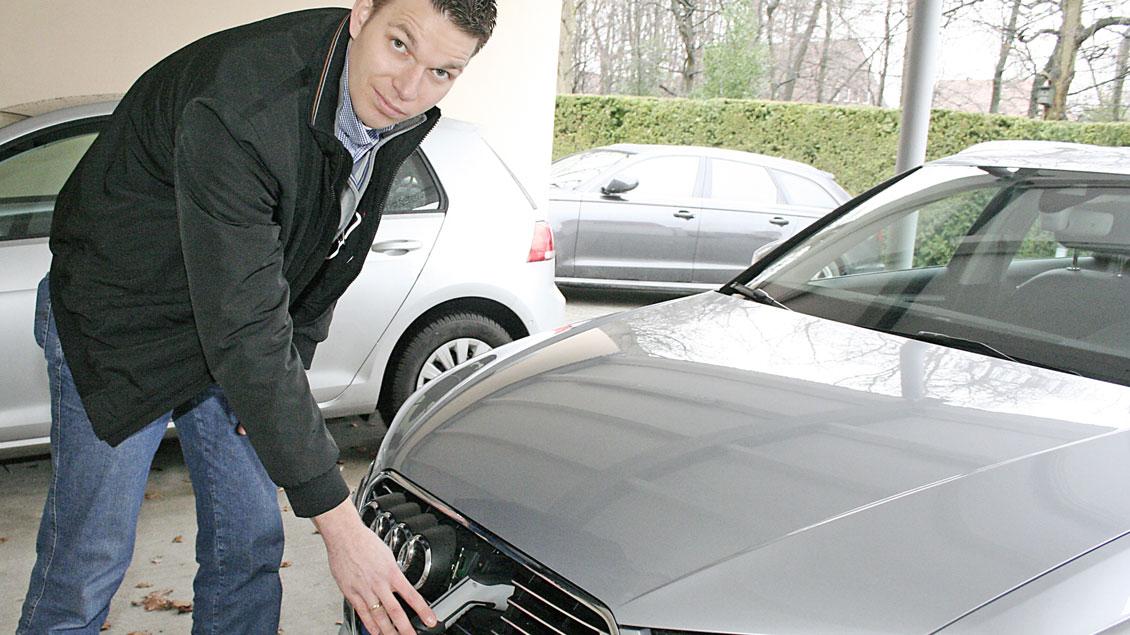 Christoph Lehmann steckt das Ladekabel in den Stromanschluss des Hybrid-Dienstwagens. Die übrigen Fahrzeuge im Offizialats-Fuhrpark fahren mit Dieselkraftstoff.