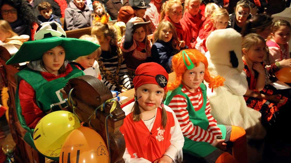 Kinder mit farbenprächtigen Kostümen füllen in der Karnevalsmesse die Bänke in der Rheinberger Kirche St. Peter.