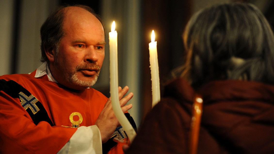 """Durch zwei brennende Kerzen wird der Blasius-Segen gesprochen: """"Auf die Fürsprache des heiligen Blasius bewahre dich der Herr vor Halskrankheit und allem Bösen."""""""