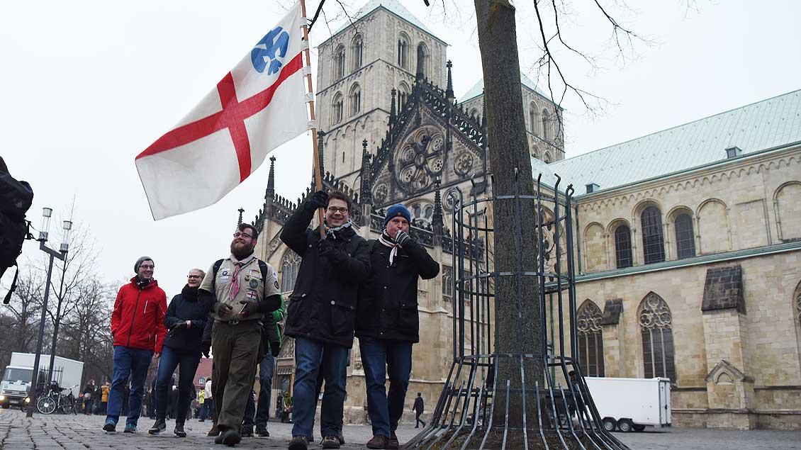 Die Pfadfinder kommen! Eine Gruppe der Deutschen Pfadfinderschaft St. Georg (DPSG) im Bistum Münster zieht mit iher Fahne über den Domplatz Richtung Demonstration. | Foto: Michael Bönte