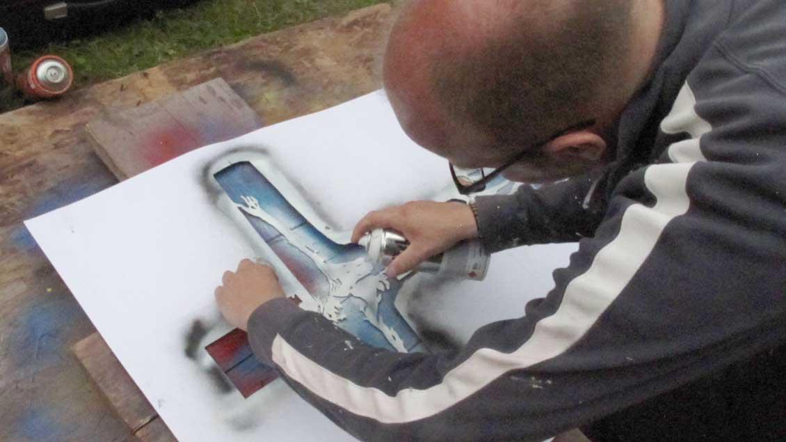 Künstler und Sozialarbeiter Mika Springwald sprayt Christus am Kreuz.
