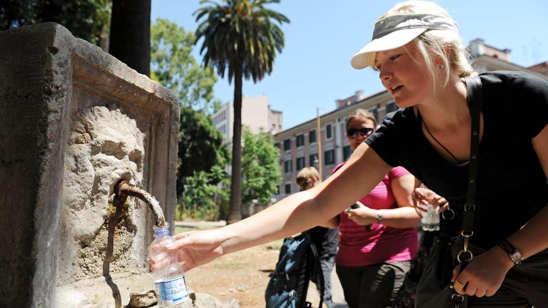 Wasserzapfen aus einem öffentlichen Trinkbrunnen in der Hitze Roms.