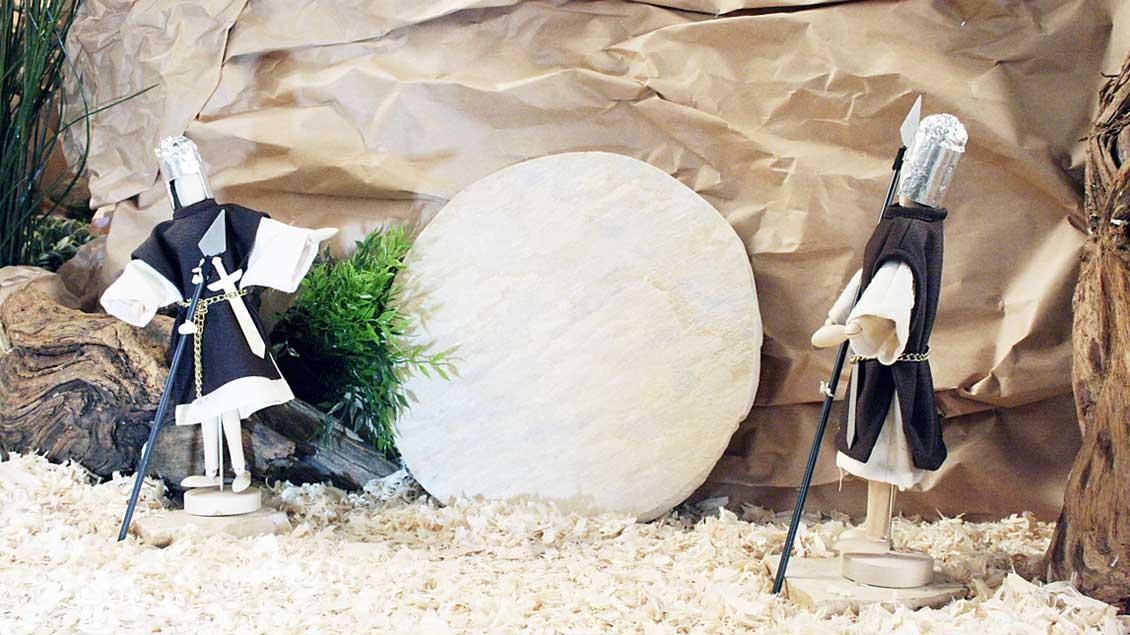 Zwei Soldaten bewachen das Grab Jesu mit dem runden Grabstein davor.