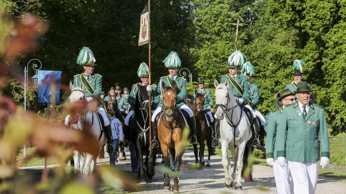 Reitende Schützen in Grünrock und Schützenhut bei einer Reiterprozession.