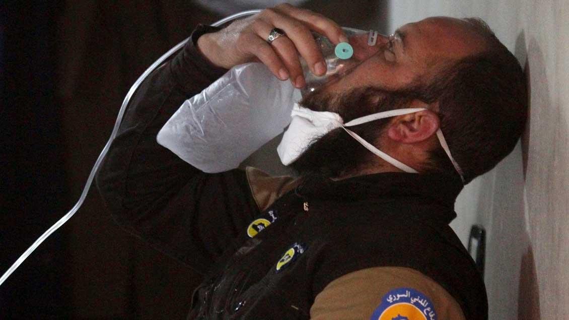 Ein Mitarbeiter des Zivilschutzes atmet in eine Sauerstoffmaske in der Gegend des mutmaßlichen Giftgas-Angriffs in Syrien.