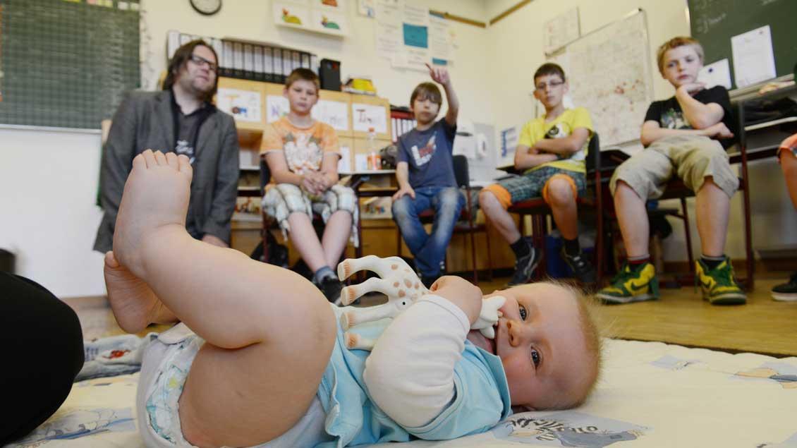 So geht Babywatching: Gemeinsam mit Schulseelsorger Christoph Moormann (hinten links) schauen die Förderschüler dem Kind beim Spielen zu.
