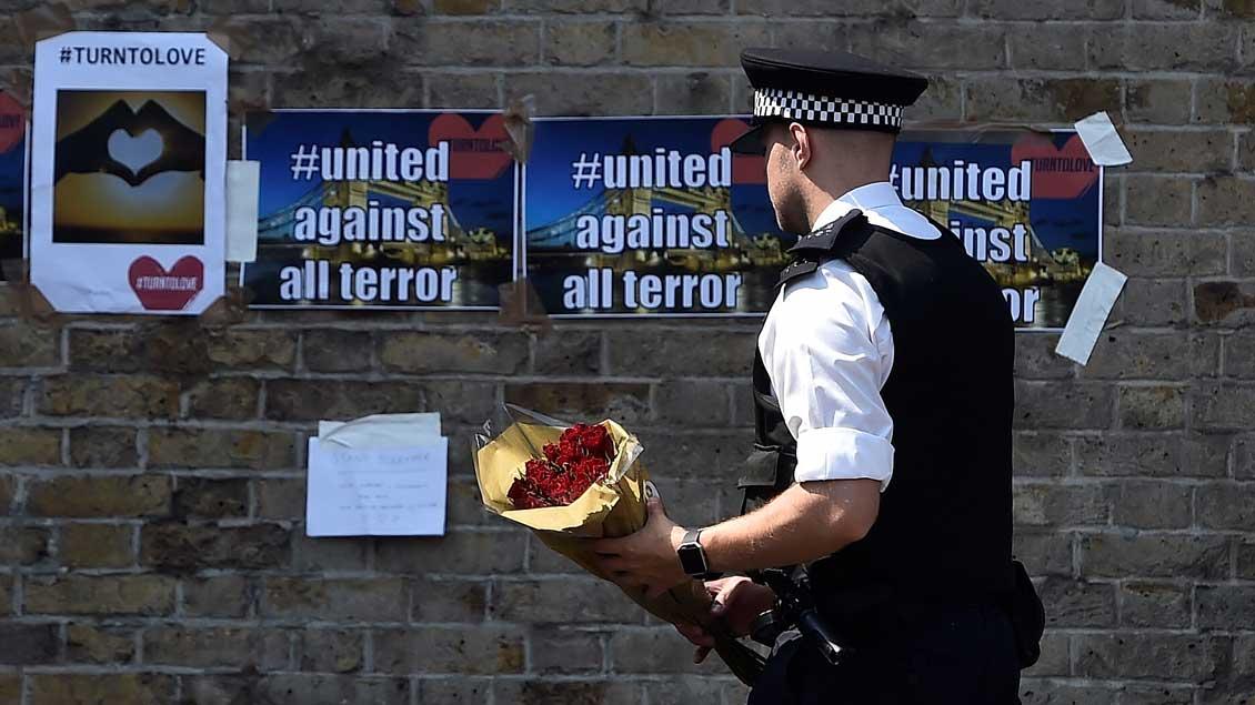 Ein Polizist mit Blumen.