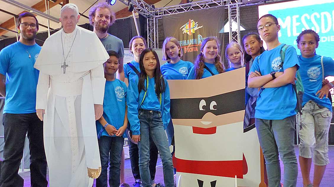 Alle elf Messdiener der Gemeinde Moordeich St. Paulus waren nach Vechta gekommen (hier mit einem Papstfoto auf Pappe auf der Bühne in der Veranstaltungshalle). | Foto: Franz Josef Scheeben
