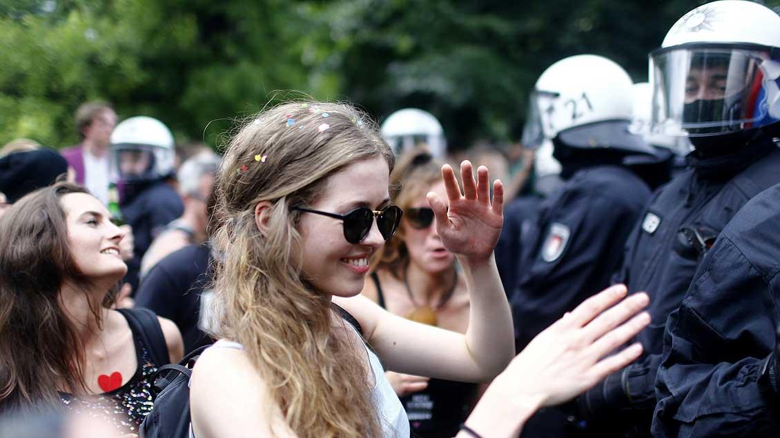 """Es geht auch friedlich: Während der Demonstration """"Hamburg zeigt Haltung"""" tanzt diese junge Frau vor den Polizisten. Auch das kirchliche Bündnis """"Global gerecht gestalten"""" nahm teil."""