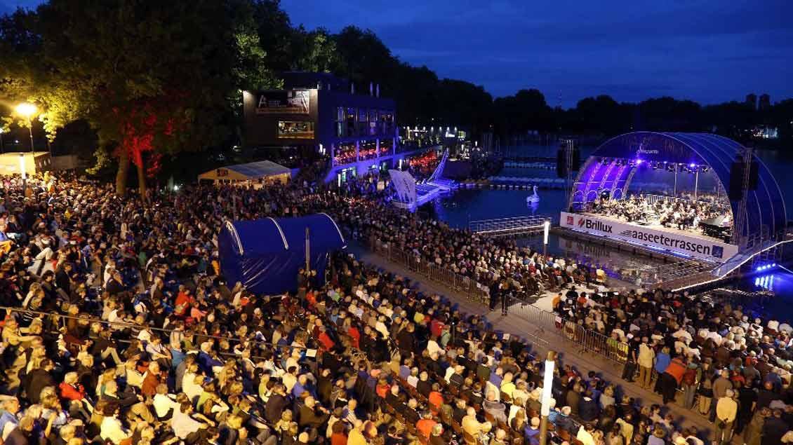 """Die Seebühne am Aasee in Münster steht für die beeindruckende Kulisse der """"AaSeerenaden"""", die vor allem bei anbrechender Dunkelheit für ein besonderes Flair sorgt."""