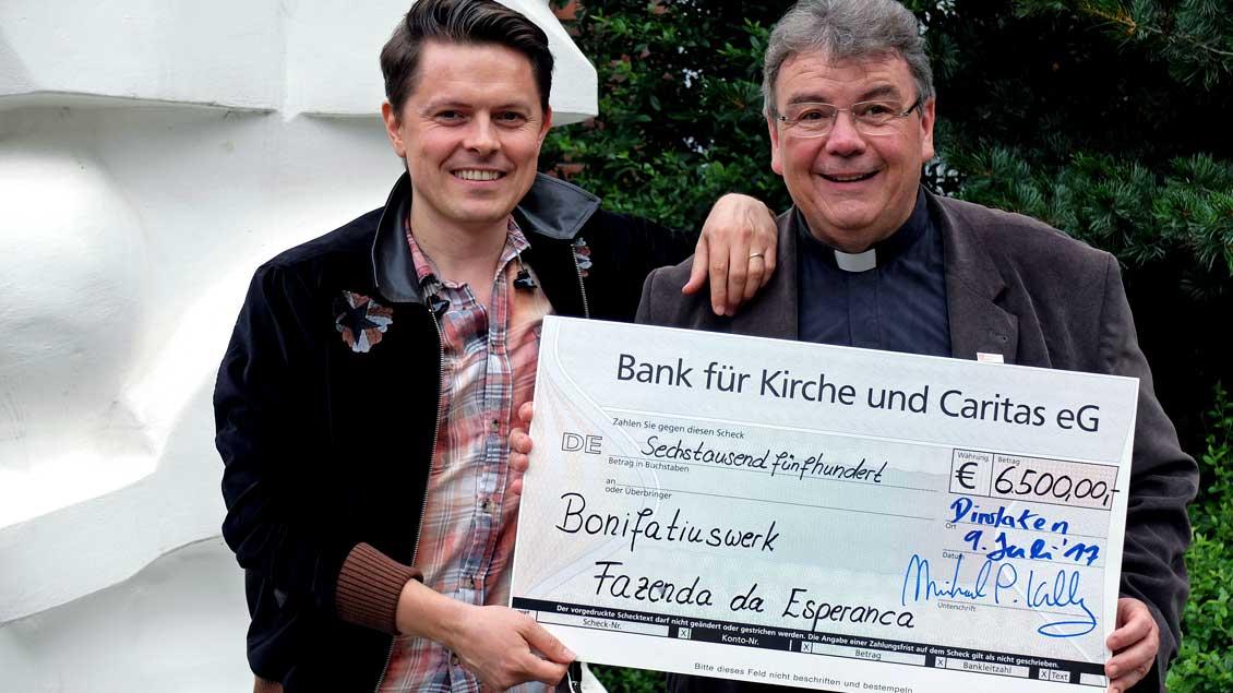 Michael Patrick Kelly (links) und Georg Austen vom Bonifatiuswerk bei der Scheckübergabe.