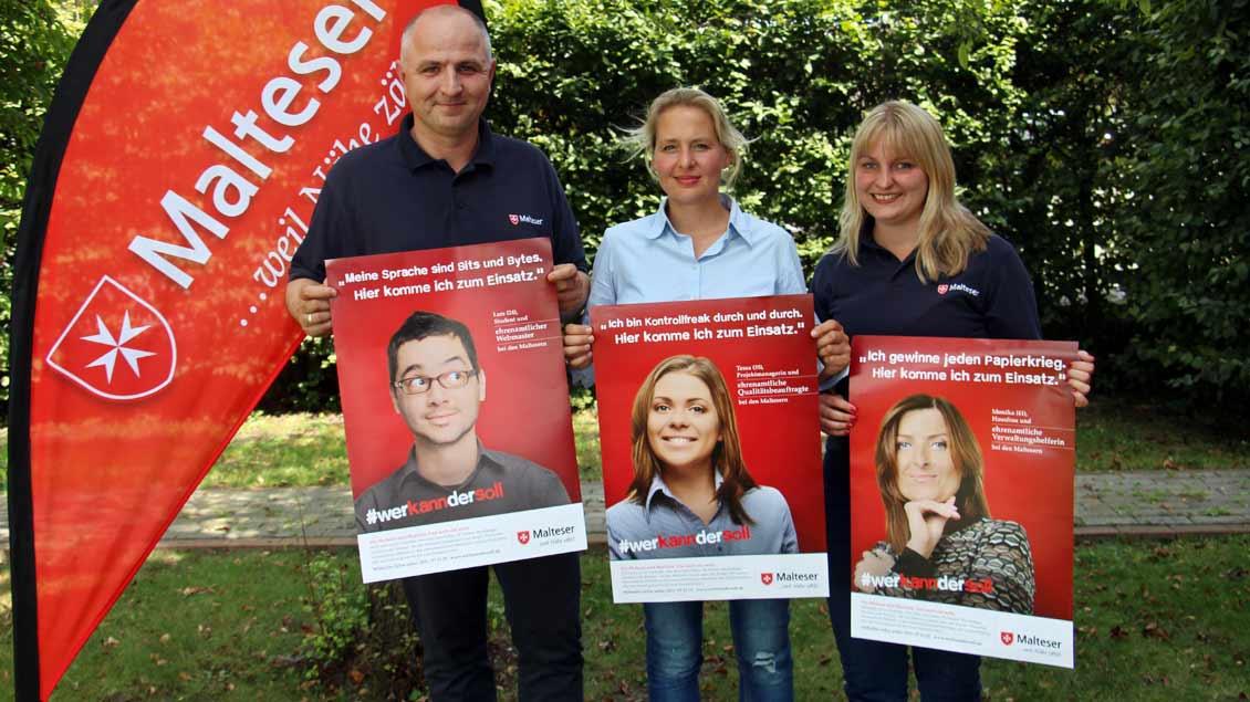 Präsentieren die Plakate zur Kampagne #werkanndersoll: Stephan von Salm-Hoogstraeten (Malteser Diözesangeschäftsführer), Julia Schulte (Agentur Prachtstern) und Jennifer Clayton (Malteser Diözesanpressereferentin).