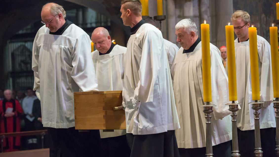 Messdiener tragen den schlichten Eichensarg bei der Begräbnisfeier im Kölner Dom.