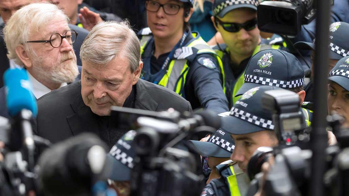 Kardinal George Pell bahnt sich mit Hilfe der Polizei einen Weg durch die Medienvertreter in den Gerichtssaal.