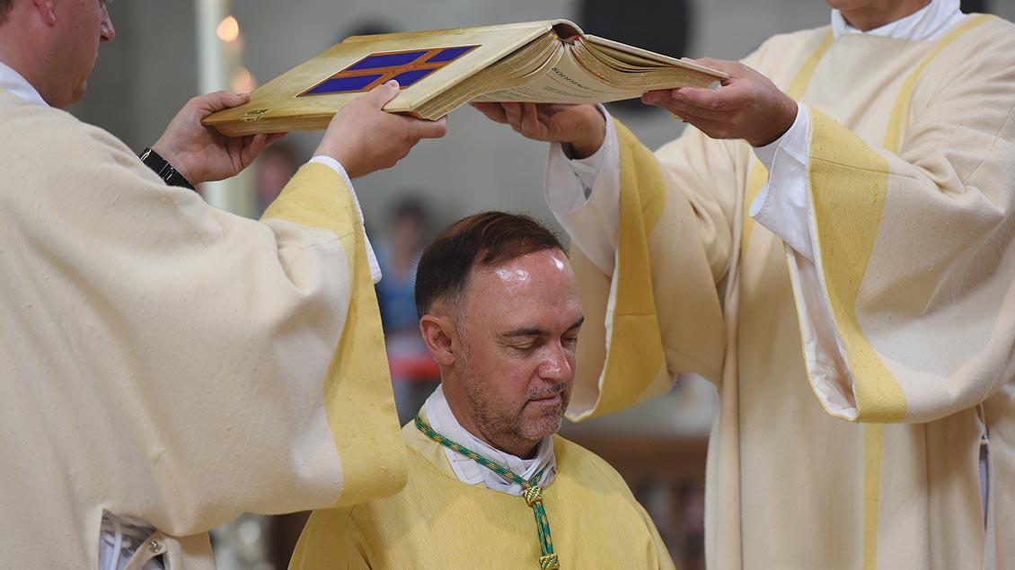 Während der Weihe-Liturgie wird dem Weihbischof das Evaneliar über den Kopf gehalten. | Foto: Michael Bönte