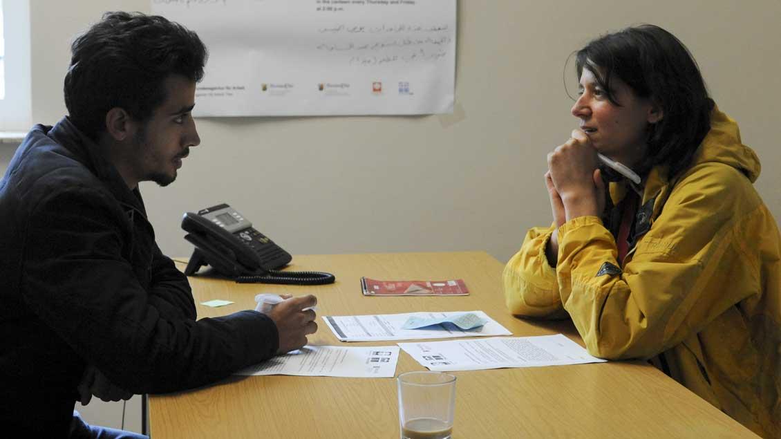 Ein syrischer Flüchtling im Gespräch mit einer Beraterin. Foto: KNA