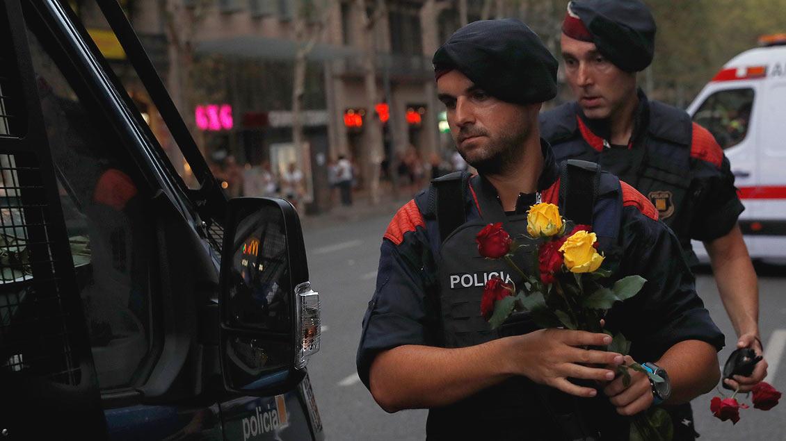 Eine Geste für den Frieden: Spanische Polizisten halten Rosen, die sie von den Demonstranten am Samstag in Barcelona geschenkt bekommen haben.