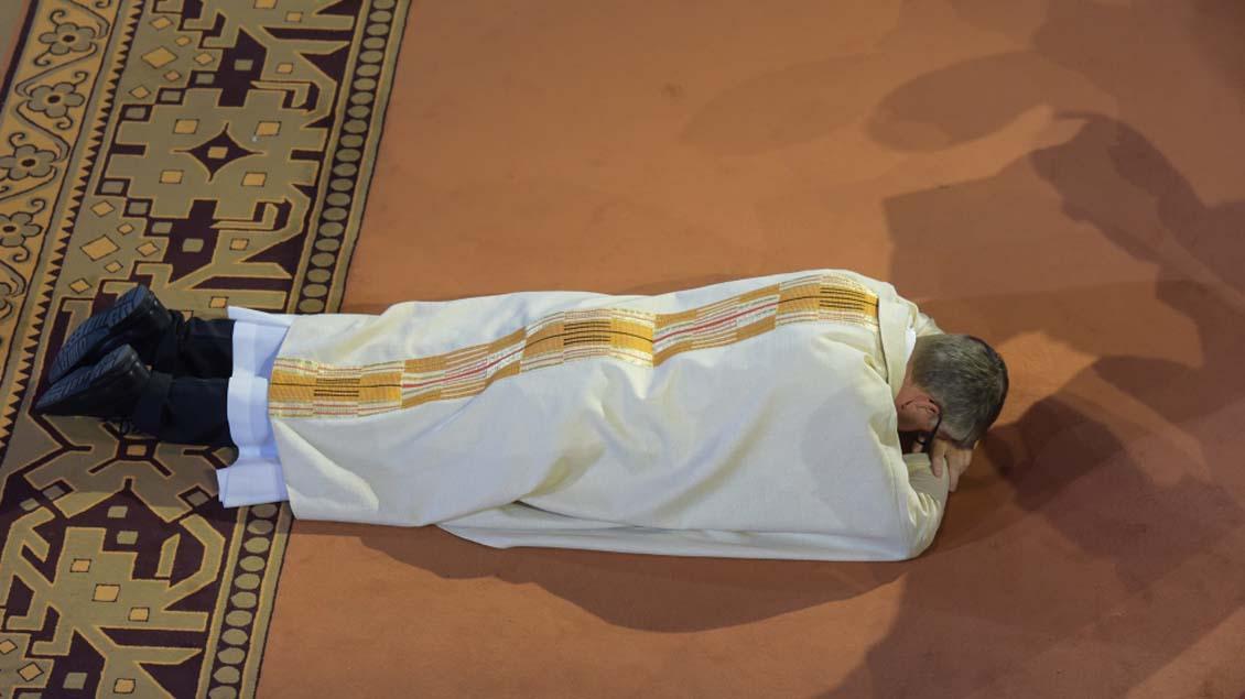Peter Kohlgraf liegt während der Allerheiligenlitanei vor dem Altar flach auf den Boden.