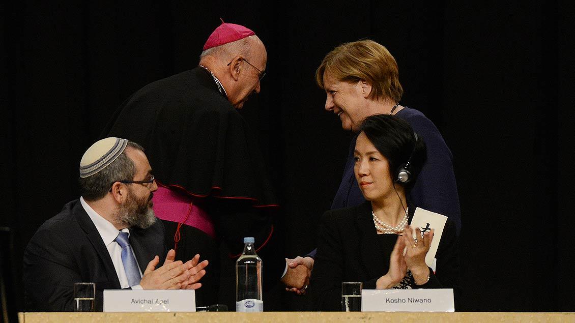 Bischof Felix Genn bedankt sich bei der Bundeskanzlerin für ihren Besuch beim Weltfriedenstreffen. | Foto: Michael Bönte