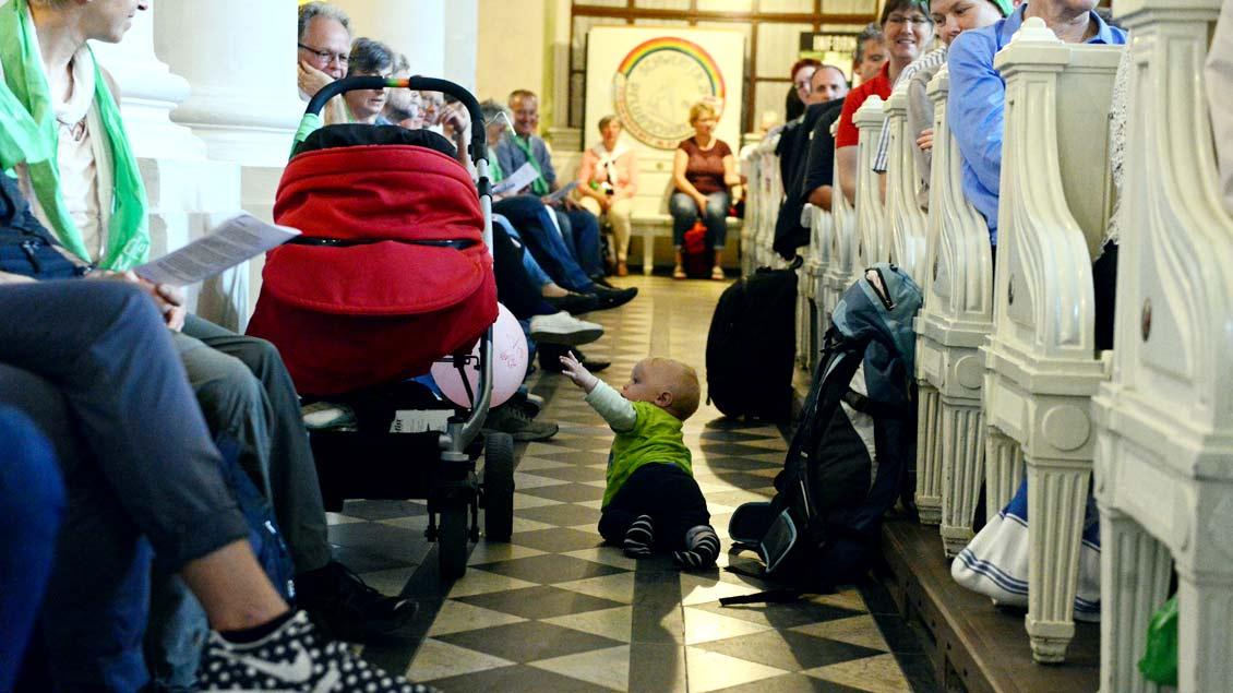 Ein Kind krabbelt durch eine Kirche.